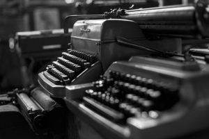 A picture of two old typewriters/keyboards - Use our website copywriting services and you'll learn that the keyboard is king!